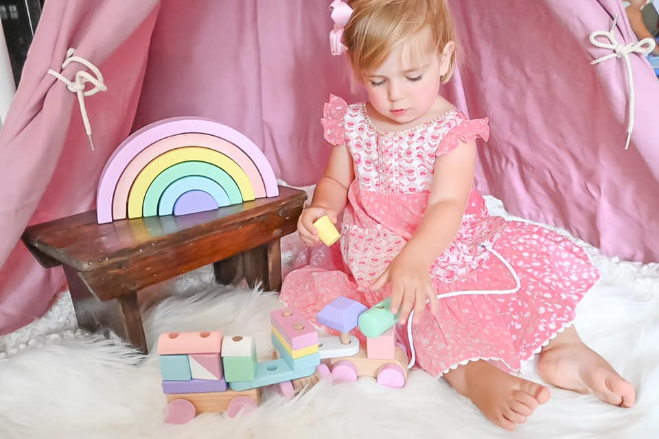Little toddler girl in a pink dress playing on a fluffy rug with a wooden train and a wooden rainbow