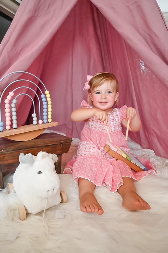 little girl in a pink dress sitting on the floor playing with a white moose and rainbow abacus
