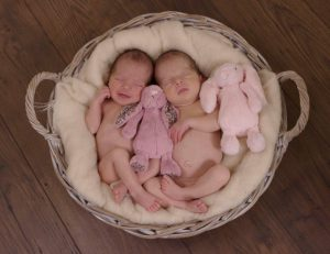 twin baby girls lying in a basket together