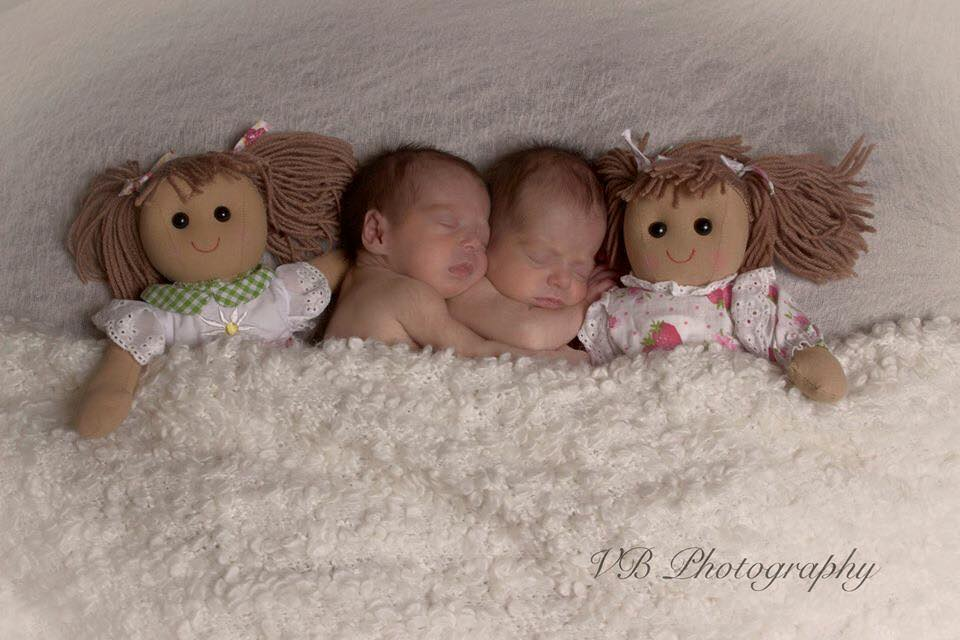 twin baby girls asleep in their cot with their dolls
