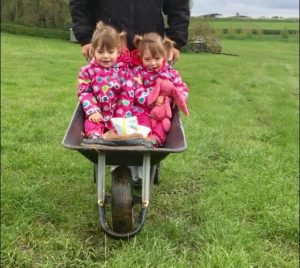 twins taking a ride in a wheelbarrow at the Dandelion Hideaway Glamping site