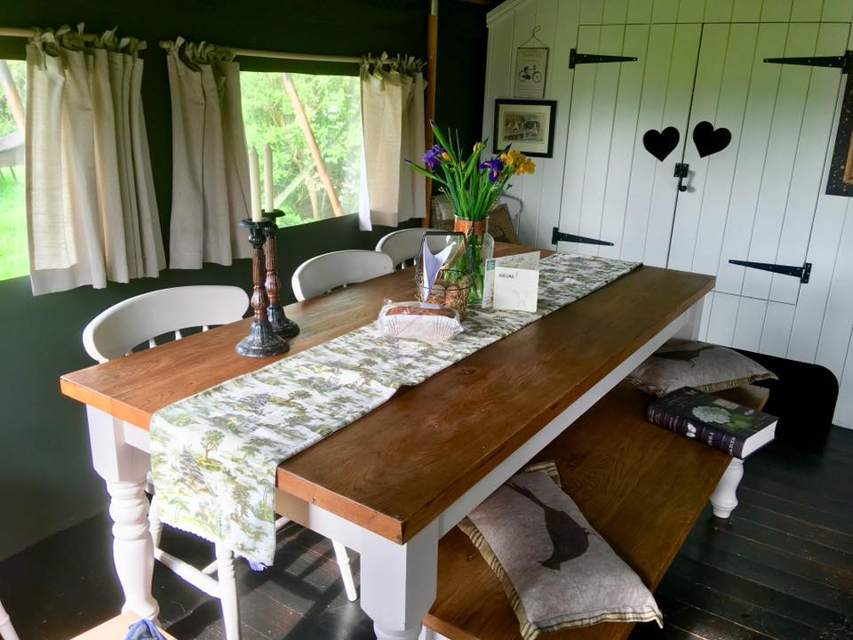 The living space at the Dandelion Hideaway showing the leather sofa, farmhouse wooden table, stove cooking range and fresh flowers on the table.