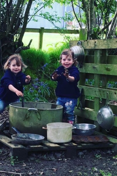 Twins playing with the mud kitchen, covered in mud. Great outdoor play ideas