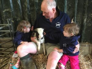 Farmer Chris and Tracey with the Popitha Twins at North Bradbury Farm with a lamb