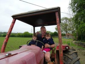 Farmer Chris with the Popitha Twins at North Bradbury Farm on a tractor