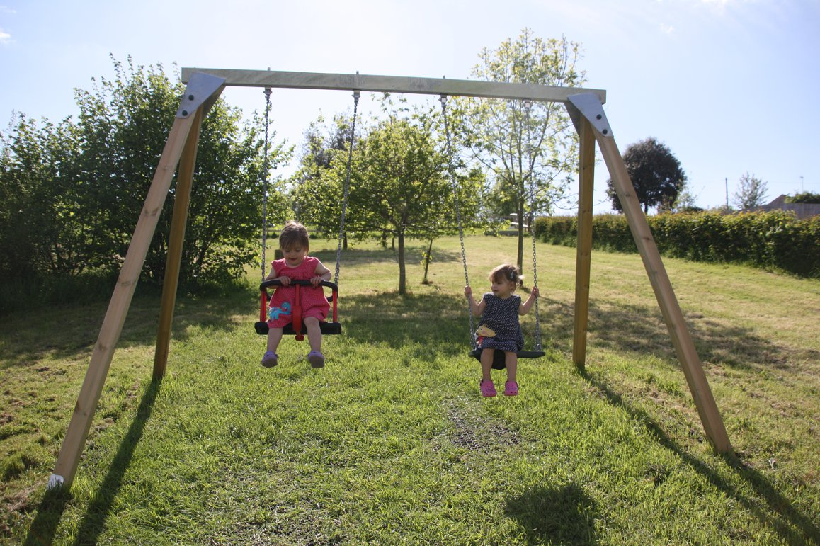 Twins playing on swings in the garden. Outdoor play ideas.