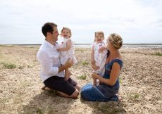 Family photos. Mum, dad, and 2 year old twin girls posing for a photo on the beach