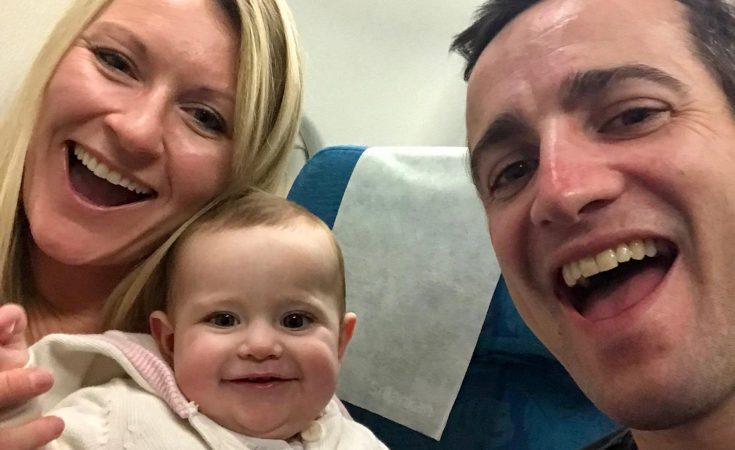 mum and dad on an airplane with a baby