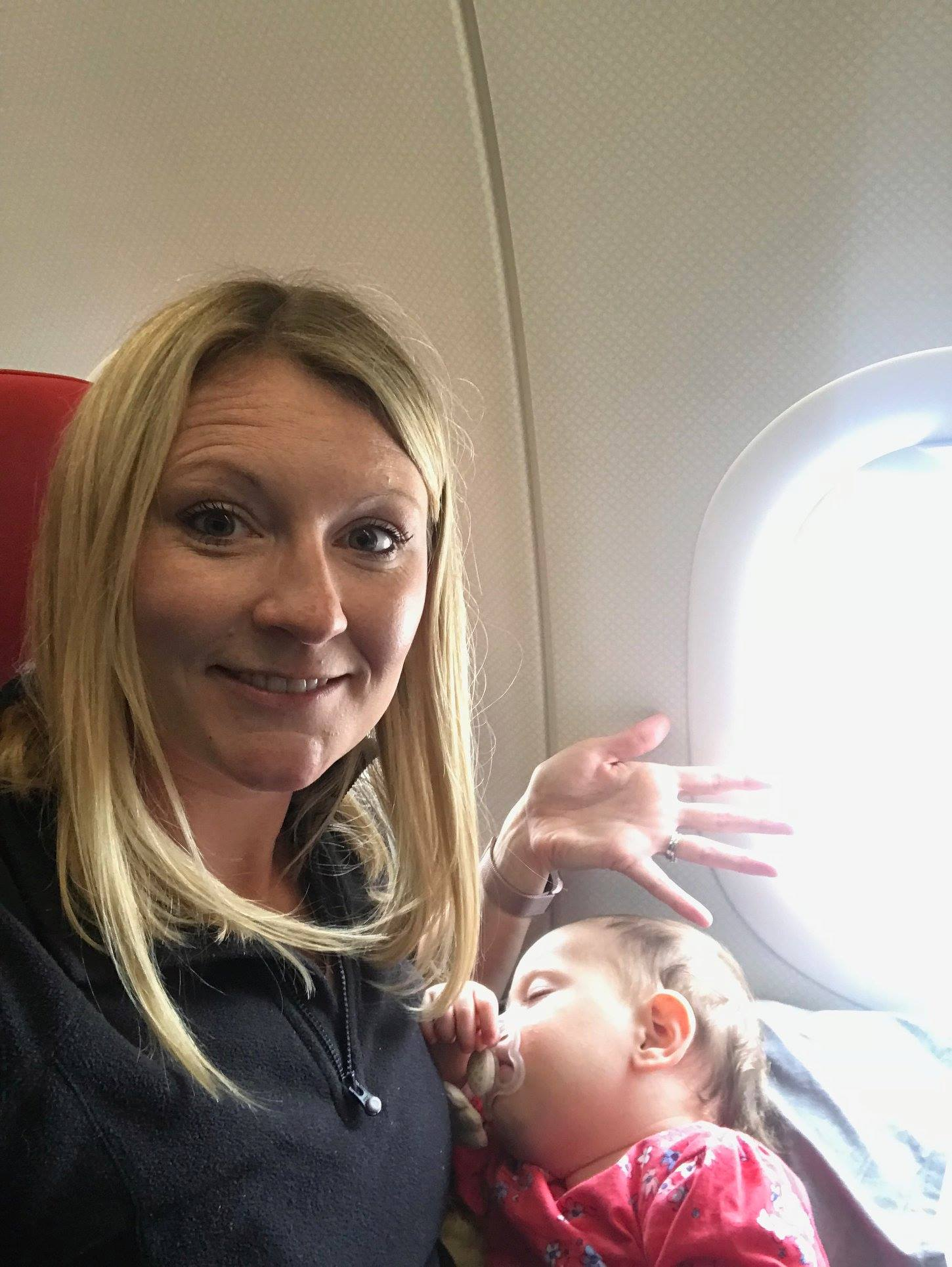 baby sleeping on mum in a airplane