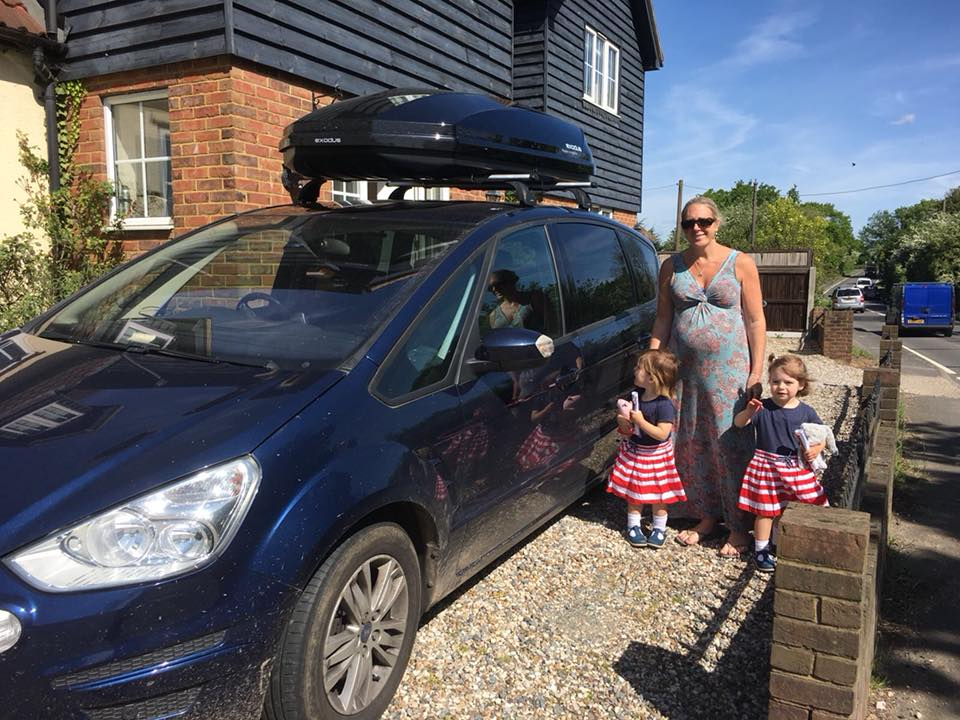 Young toddlers and mummy standing by the car ready to go on holiday