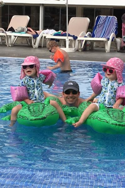 Twins with daddy in the swimming pool on holiday