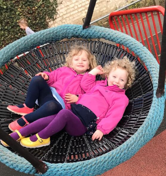 twin toddlers on a swing