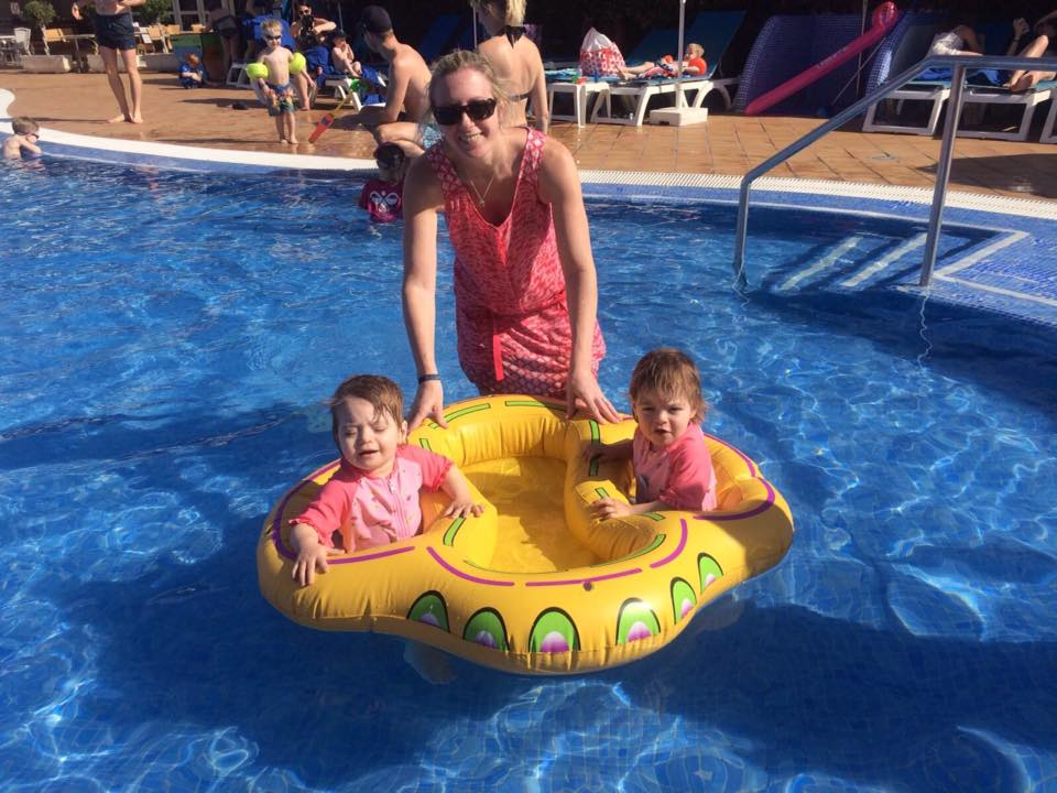 Twins on holiday in the swimming pool in a twin float with their mum