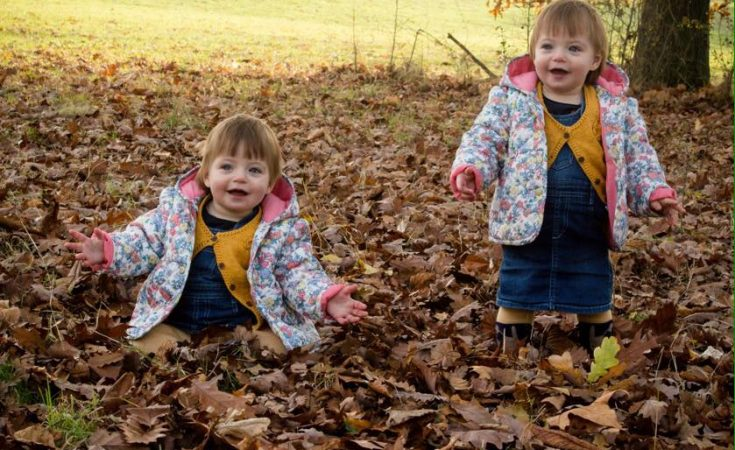 Twins playing in autumnal leaves