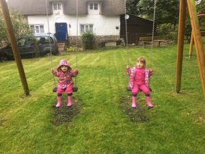 twins playing on the swings being pushed by their daddy