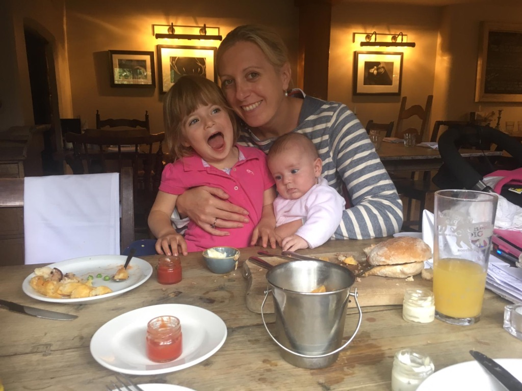 mummy sitting with two children in a pub eating a meal