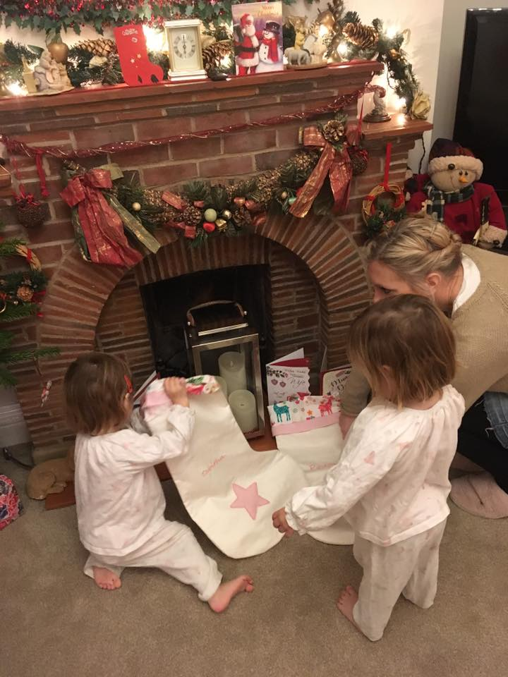 Twins putting up their Christmas stockings on Christmas eve