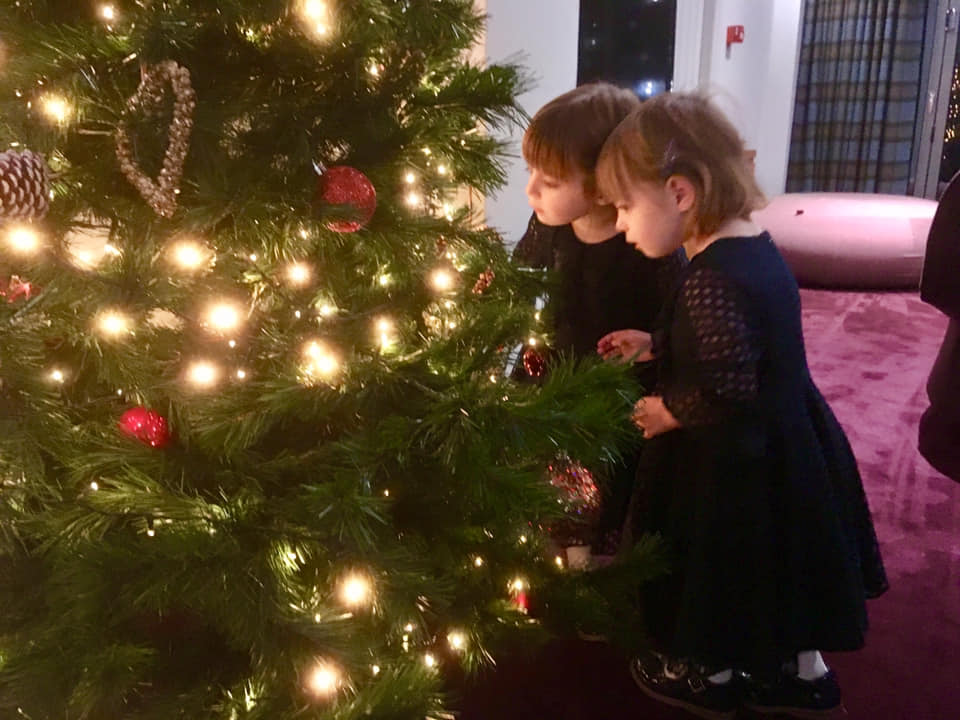 Twin 3 year old girls in blue dresses looking at the Christmas tree