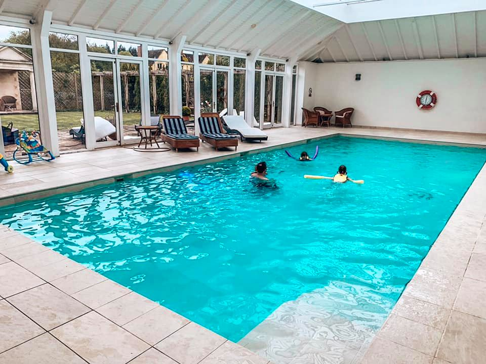 The swimming pool at Bruern Cottages in the Cotswolds with children swimming and having fun.