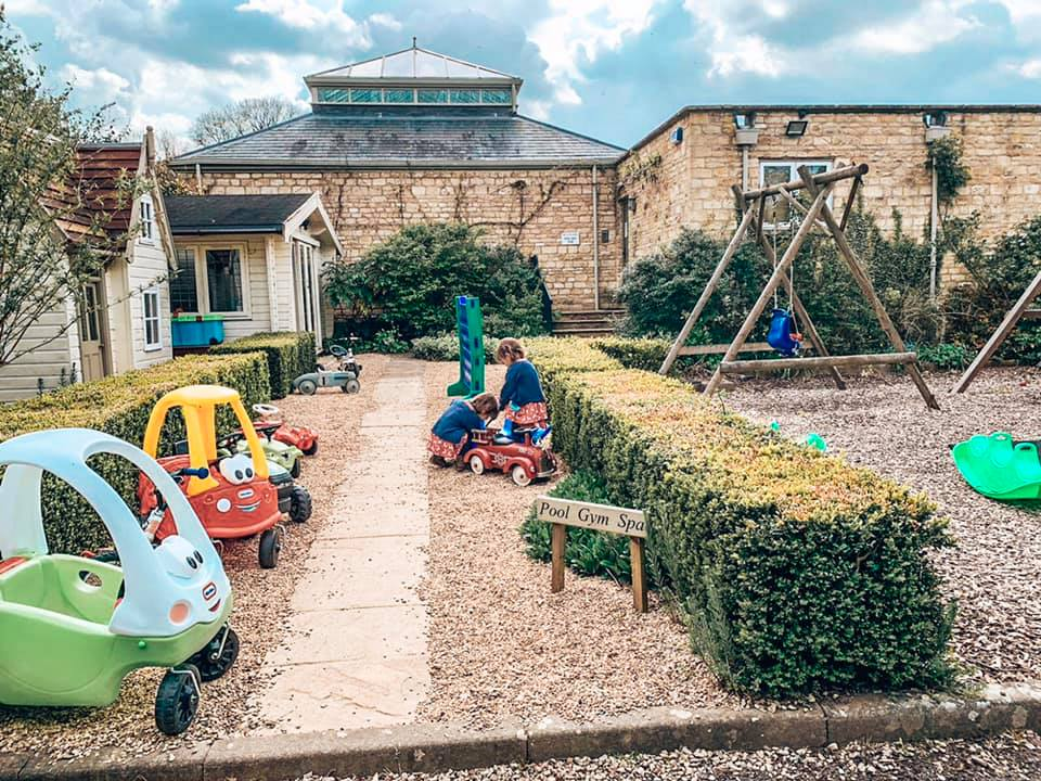 The play area at Bruern Cottages in the Cotswolds full of swings, slides, ride ons, and a play house