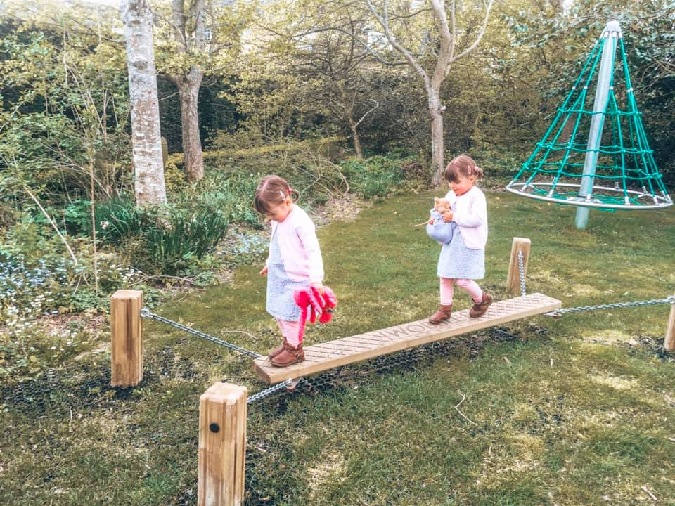 Twins playing on the outdoor play equipment at Bruern Cottages