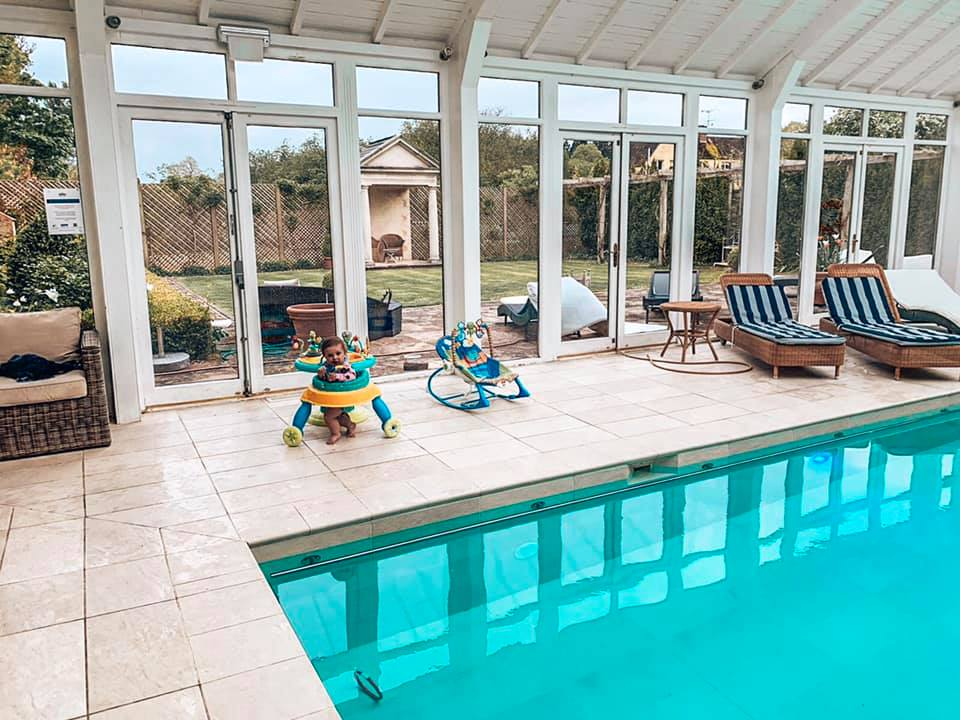The swimming pool at Bruern Cottages in the Cotswolds with baby toys at the side
