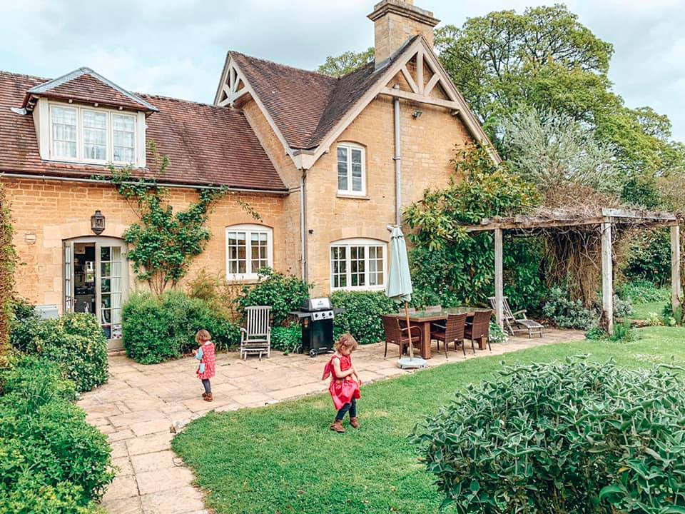 The garden in Epsom at Bruern Cottages the Cotswolds. Two children are playing in the garden.