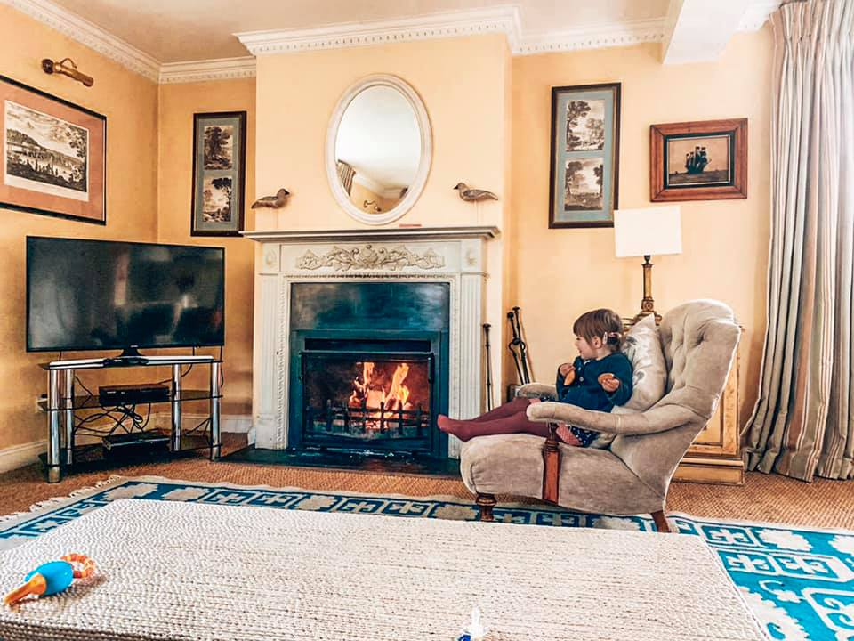 The Lounge in Epsom at Bruern Cottages the Cotswolds with a child sitting by the fire