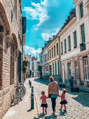 Gent, Belgium. twins and mum walking down the street.