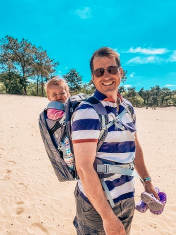 Dunes of Loon and Drunen National Park. dad carrying baby in the sand. A great place to visit in Holland with kids.