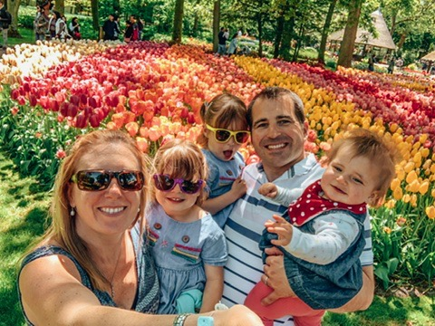 Keukonhof Tulip gardens in Holland. A family in front of a tulip bed. A great place to visit in Holland with kids.