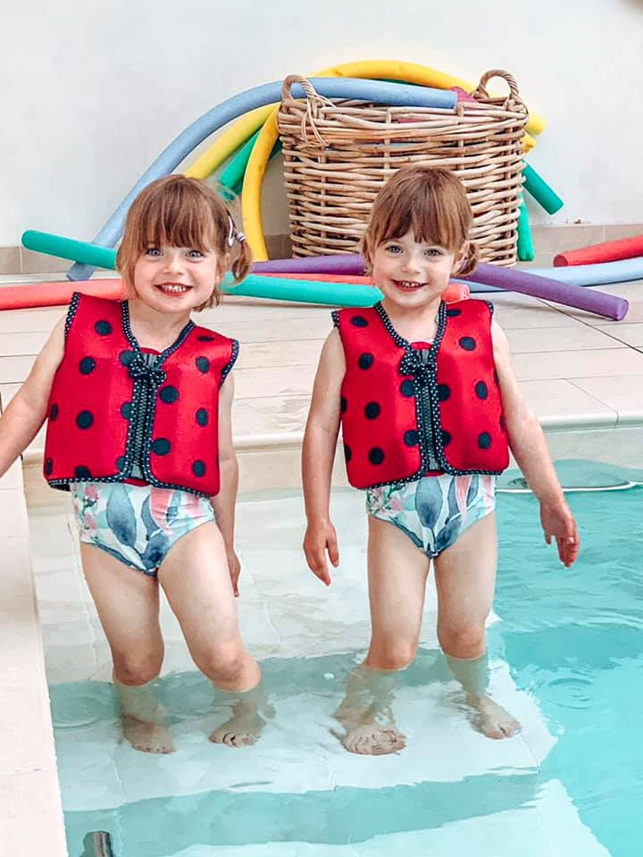 Konfidence Floatation jackets with twins playing in the water