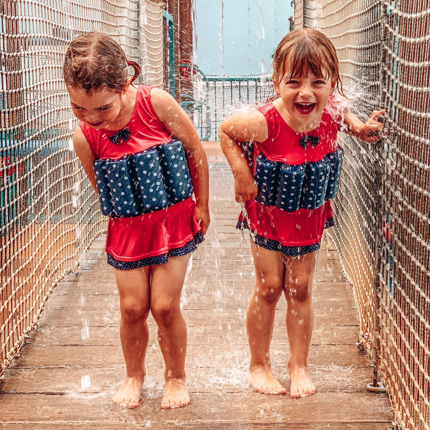 Konfidence Floatation suits with twins playing in the water