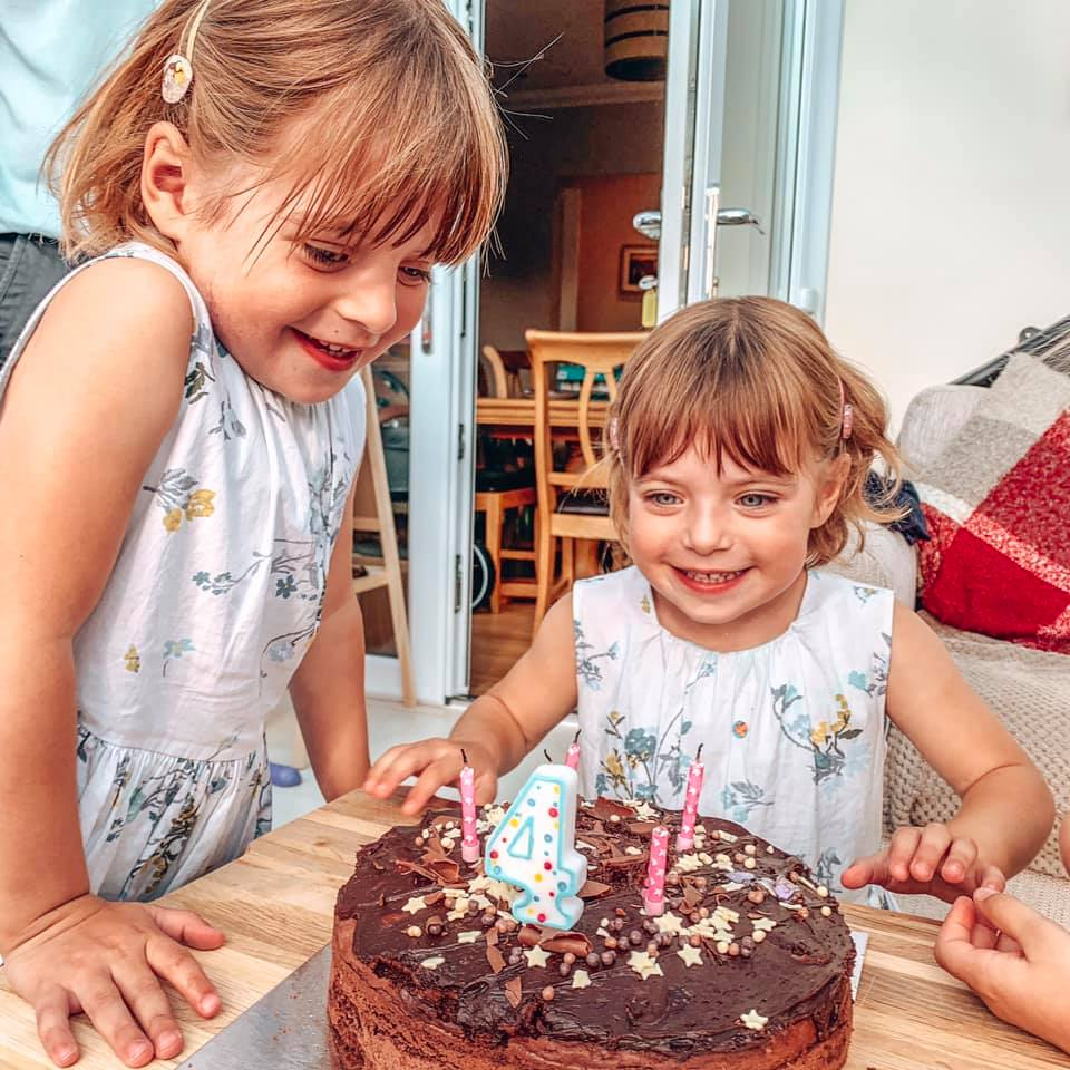 Twins celebrating forth birthday blowing out their cake