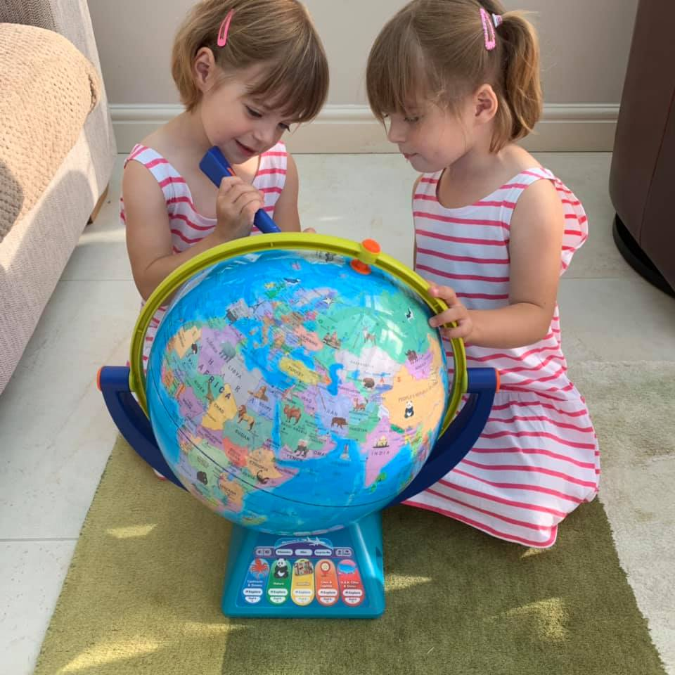 twins playing with talking globe