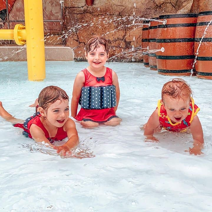 Twins and a baby playing in the water