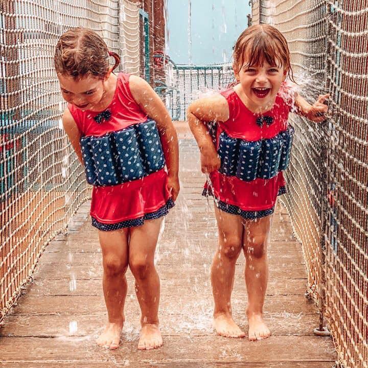 Twins splashing about under waterfalls