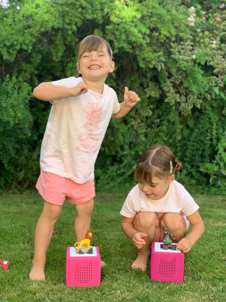 Twins dancing to their Tonie story box outside in the garden