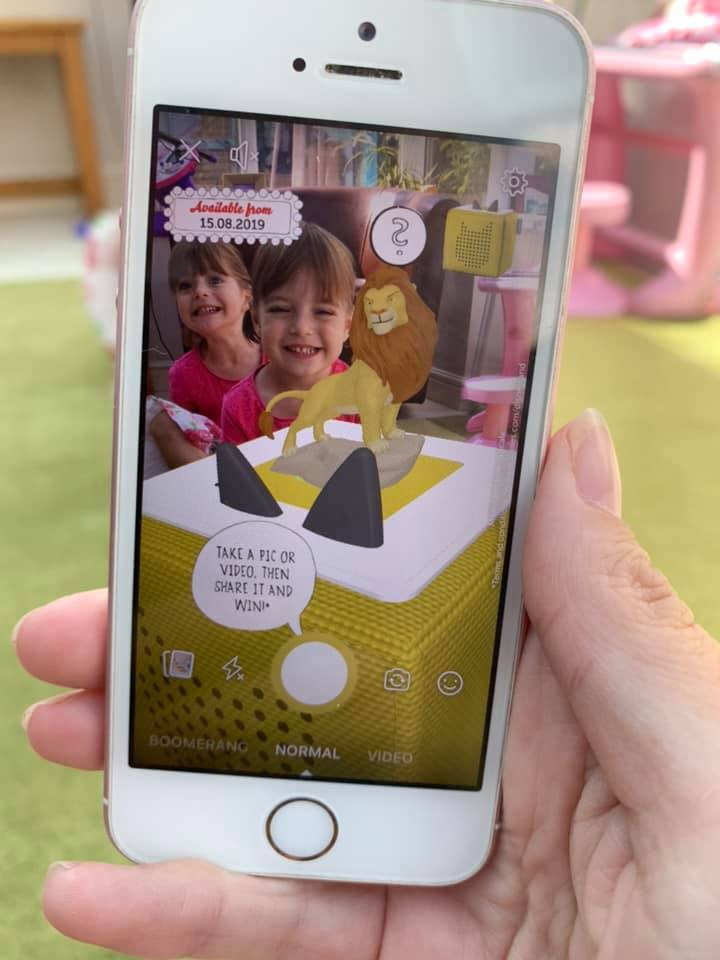 Mum playing with the new AR app for tonie taking a picture of twin girls and Simba from the Lion King