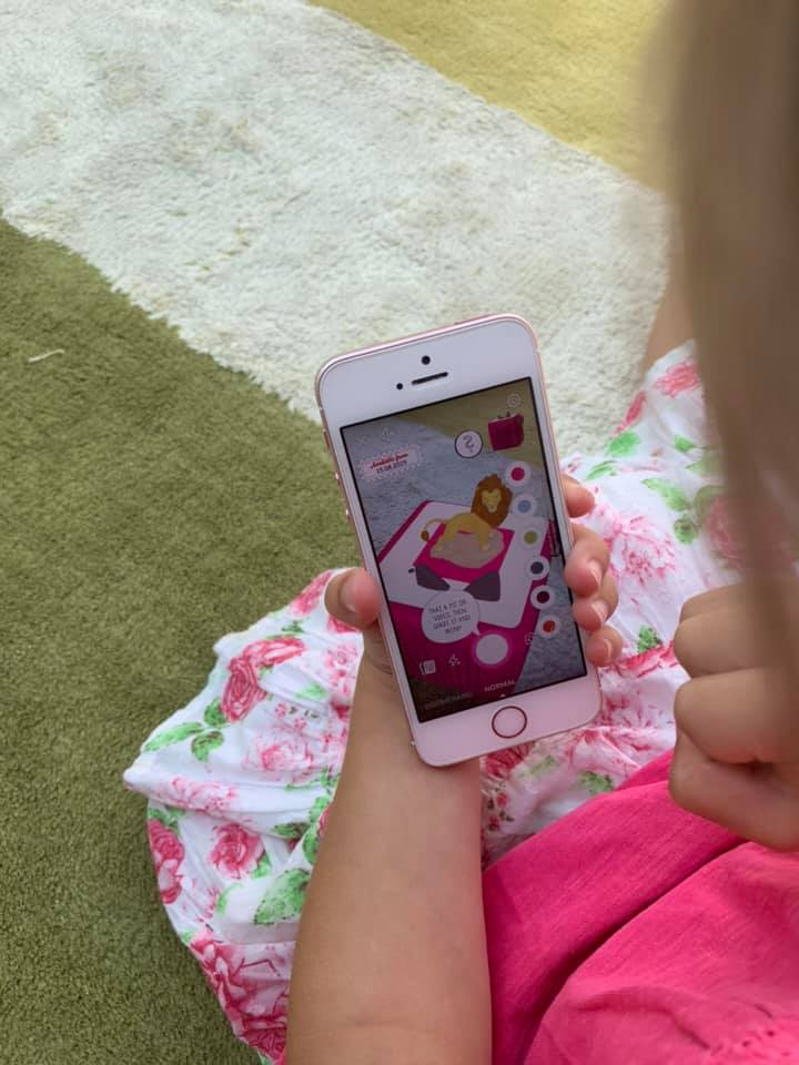 Little girl playing with an iPhone and looking at the tonie app