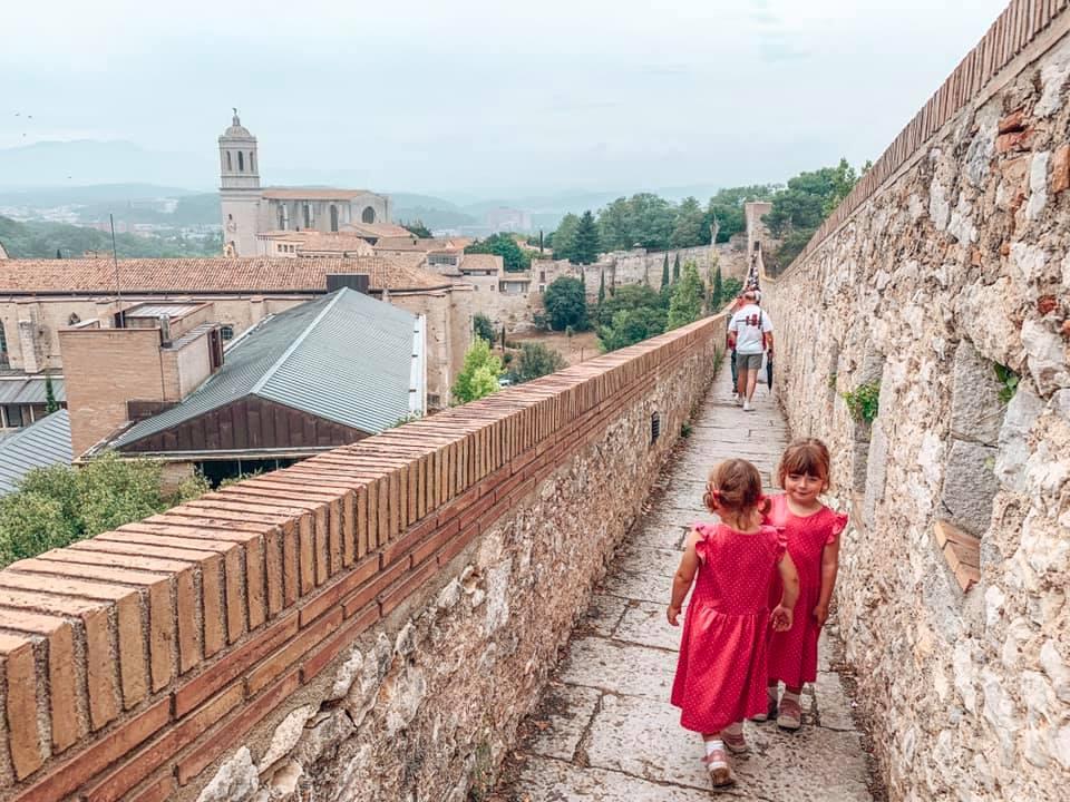 Twins walking across the Girona Wall