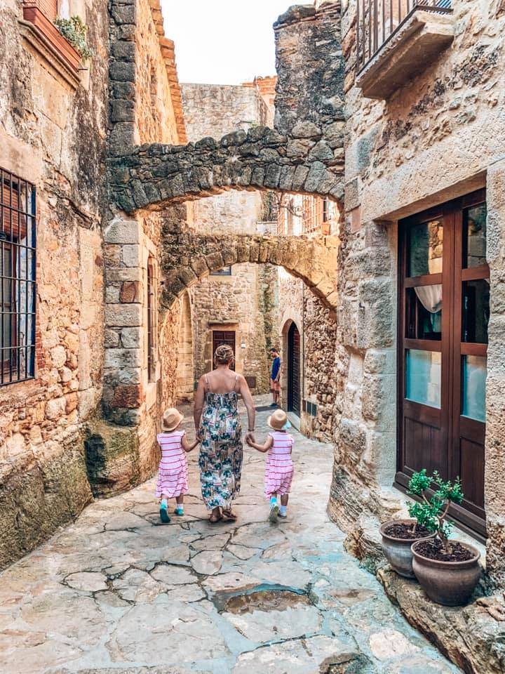 Twins and mummy walking around the cobbled streets in Pals Spain