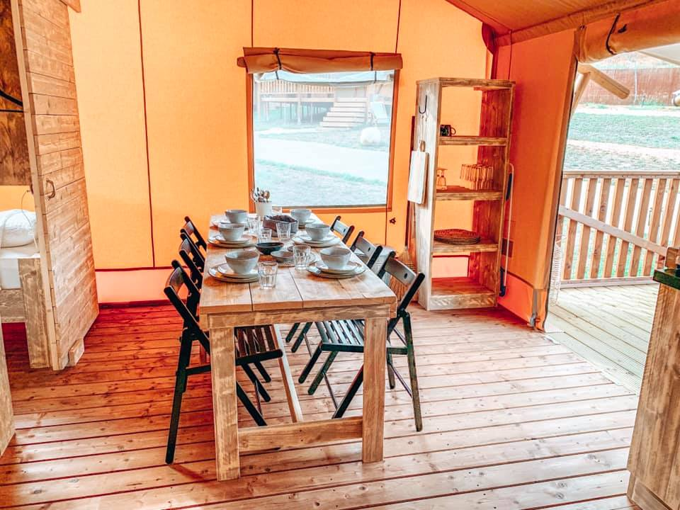 Dining area in Can Bora family lodge with table and chairs. The table is set up for dinner.
