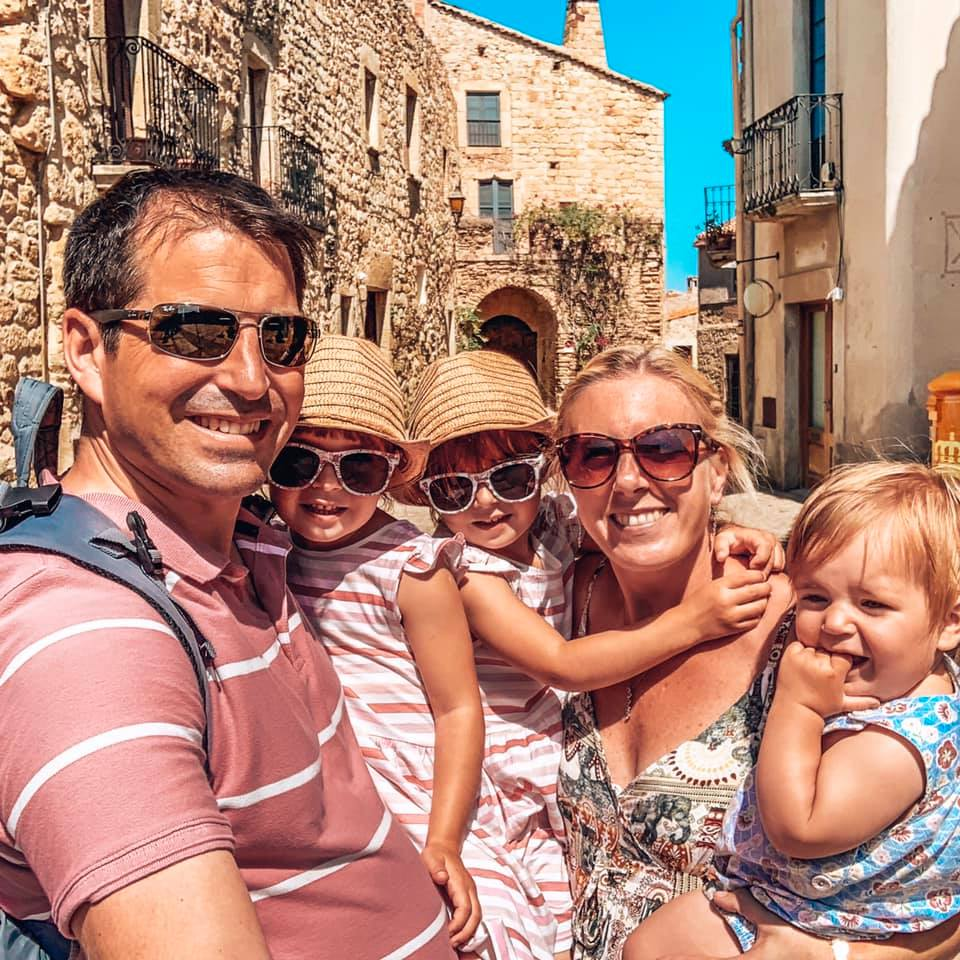 Family photo of mummy, daddy, twin girls and a baby in Pals, cobbled streets in Spain