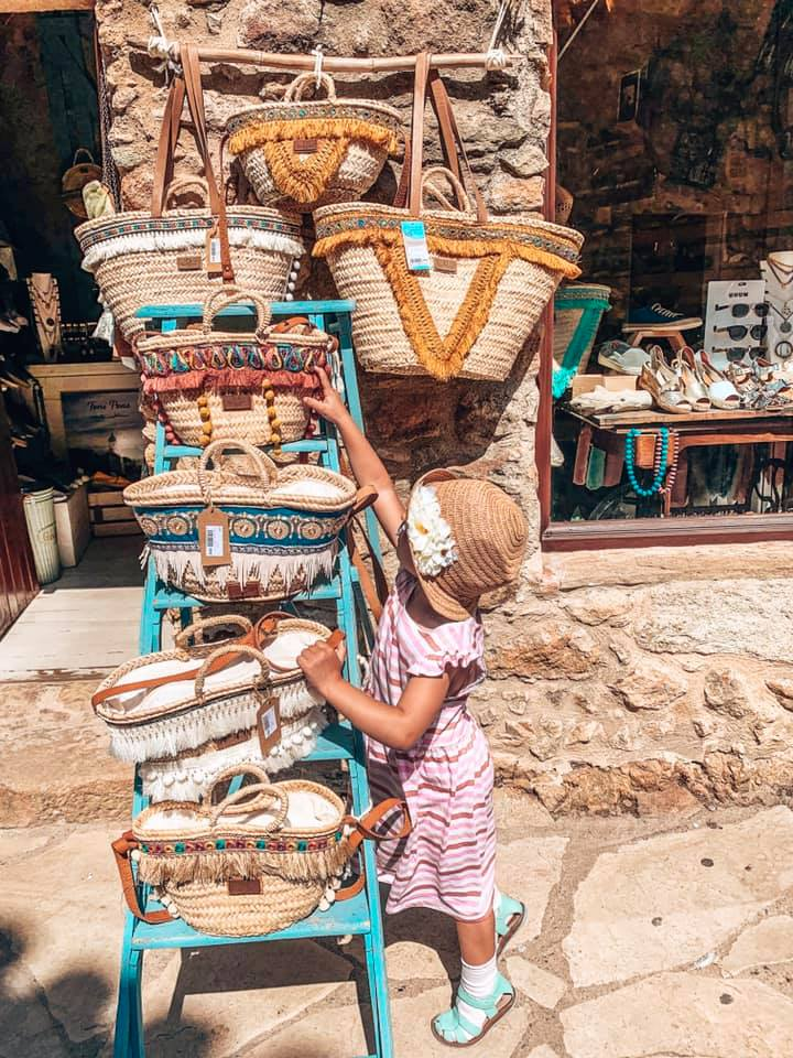 A little girl shopping for a straw bag in Pals Spain