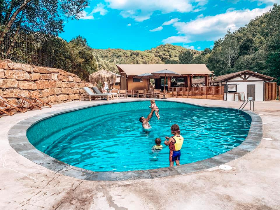 Salt water swimming pool with daddy playing with baby and twins swimming