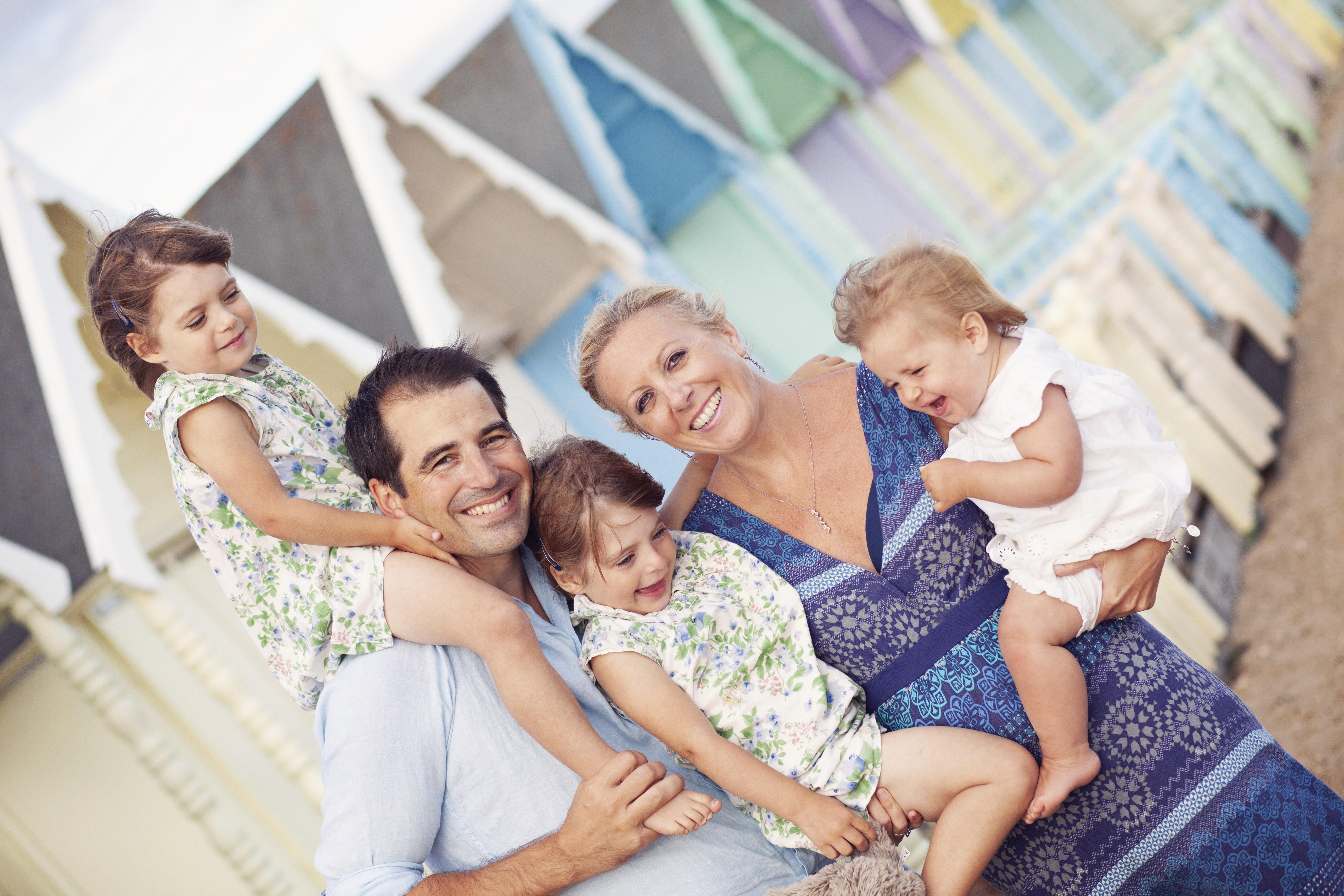 family photoshoot with beach huts as a backdrop