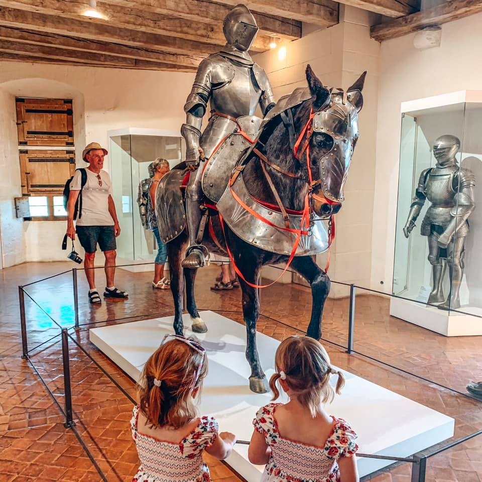 Chateau de Castelnaud - twins looking at the horse with armour