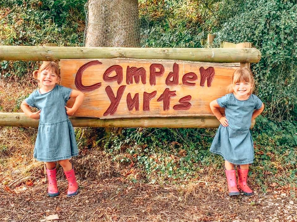 Campden Yurts sign with twins standing next to it