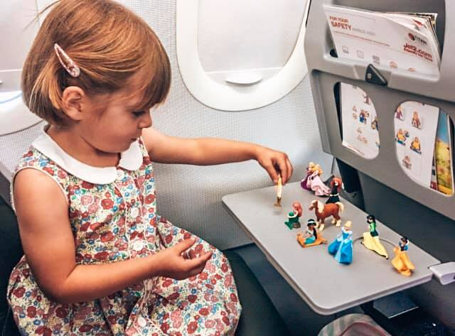 child playing with Disney figures on the airplane